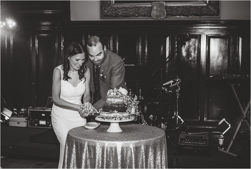Bride & Groom cutting cake at wedding reception in Trades Hall Glasgow