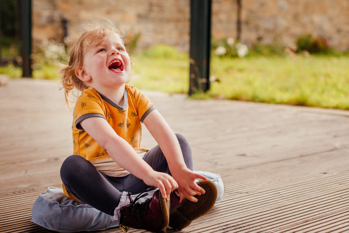 family photoshoot in barn pollok park glasgow young girl child laughing