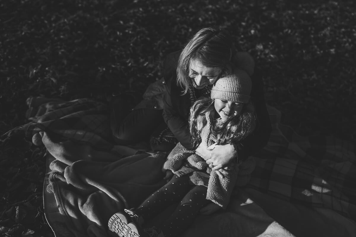 family photoshoot in glasgow park mum daughter playing around cuddling black and white