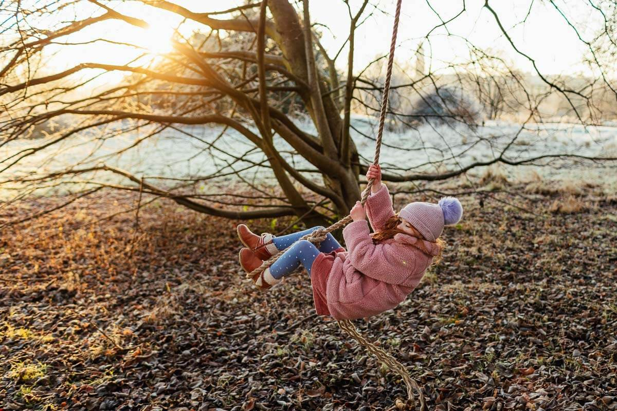 family photoshoot in glasgow park girl playing on rope swing at sunrise sunchine golden hour
