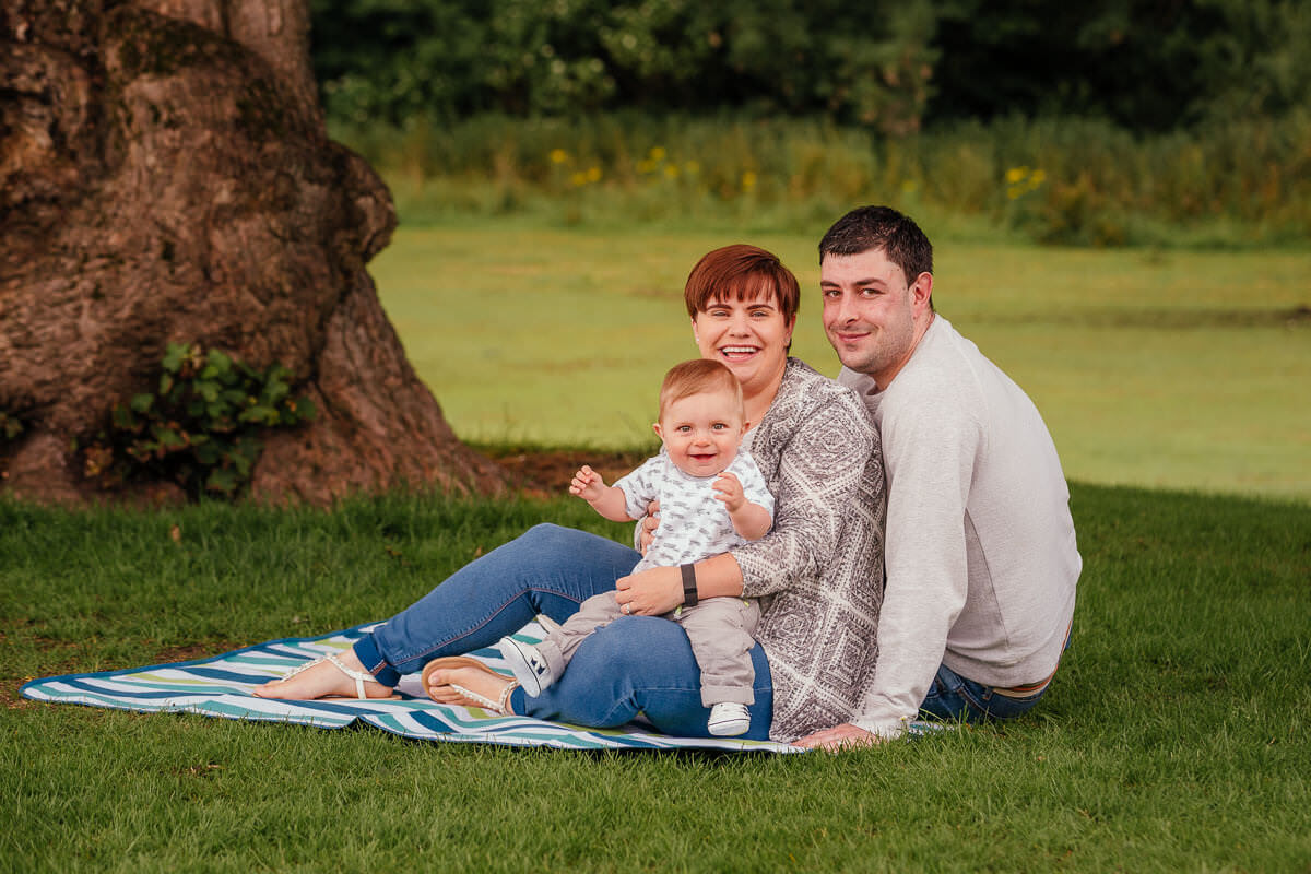 family photoshoot in aberdeen park mum dad child sitting in grass smiling