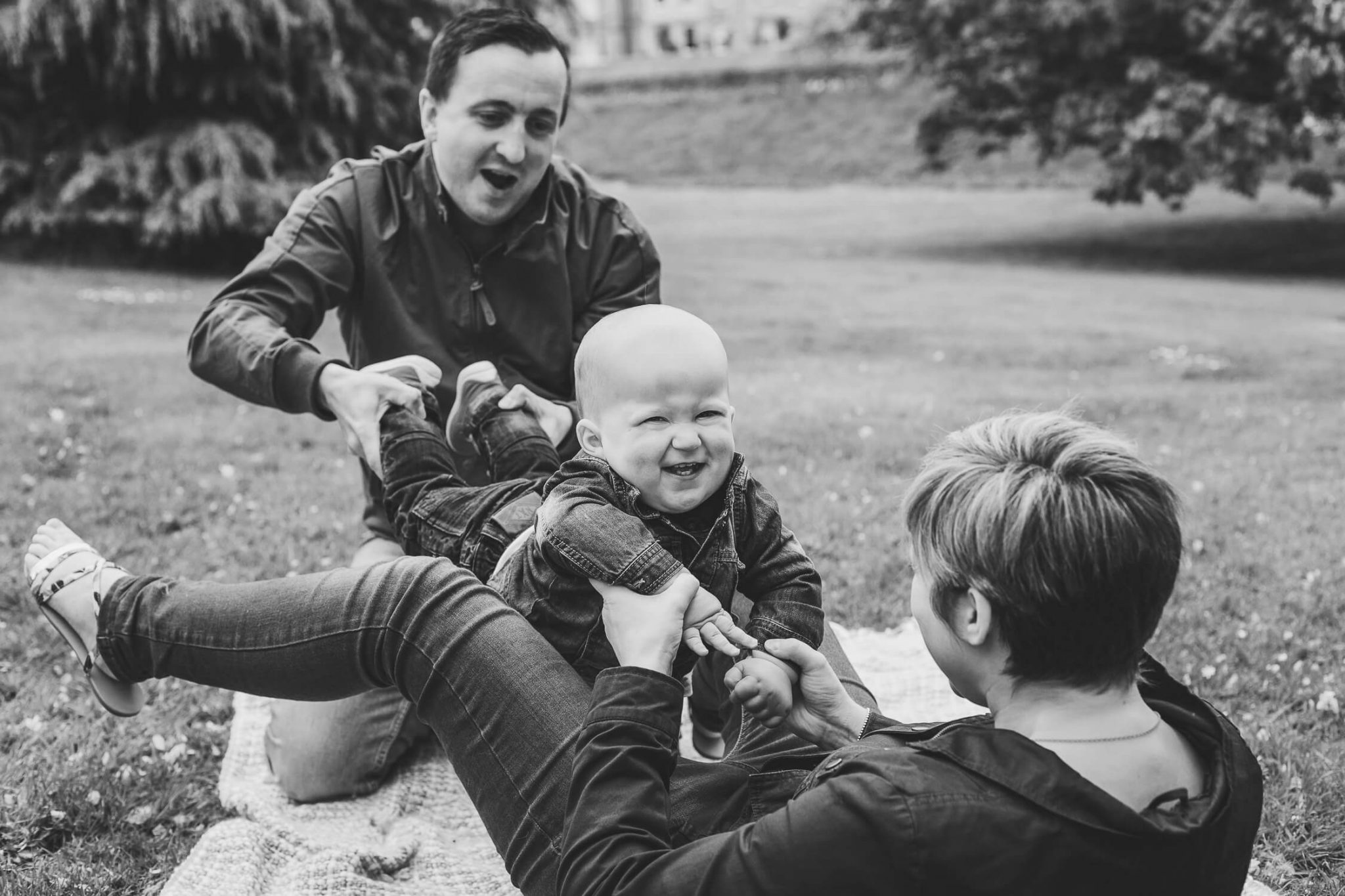 family photoshoot in aberdeen park mum dad toddler playing around black and white