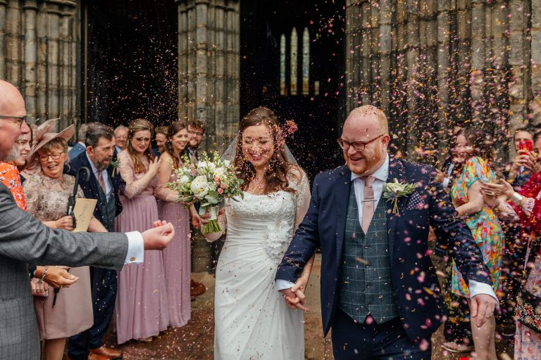bride groom leaving glasgow cathedral colourful confetti throw in brides face