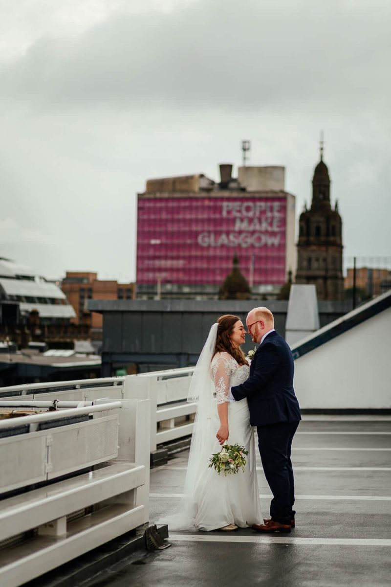 Colourful Wedding Photographer Glasgow Image of Bride and Groom in front of People Make Glasgow College sign George Square on a car park rooftop