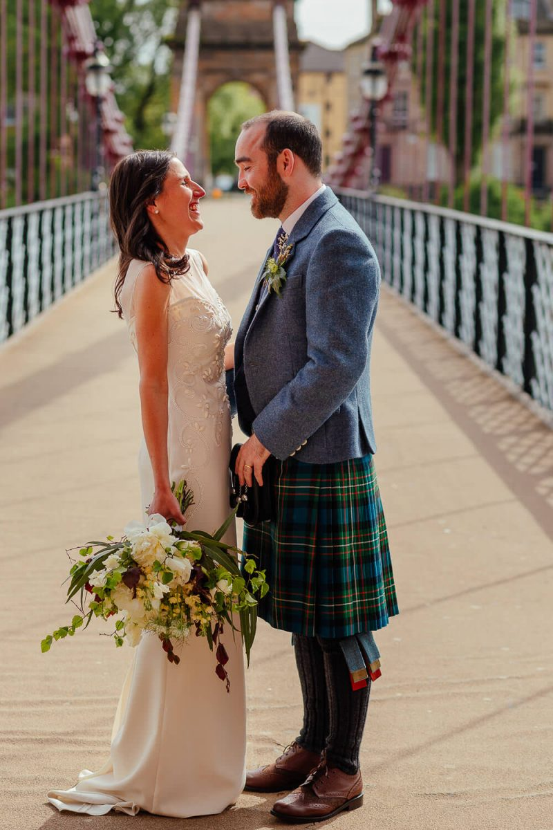 bride and groom wedding portraits on portman street bridge glasgow laughing fun colourful wedding photography glasgow