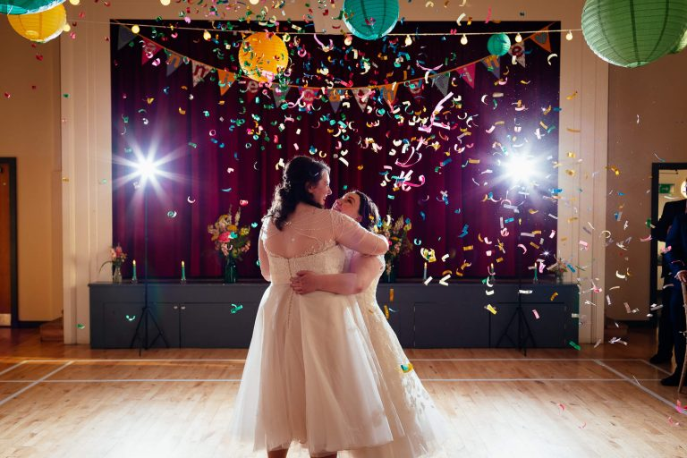 two brides wedding first dance with colourful confetti cannons at three sisters bake killearn village hall glasgow