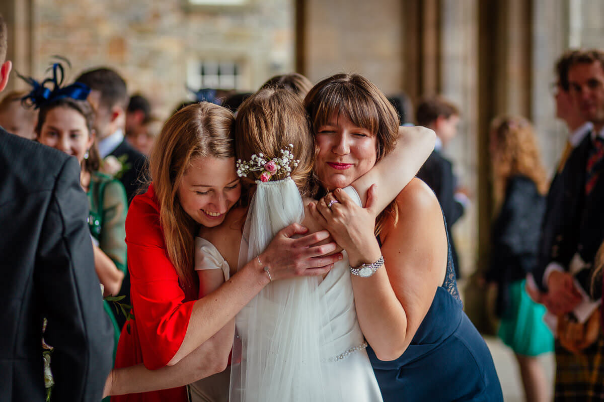 bride hugging friends after wedding st andrews