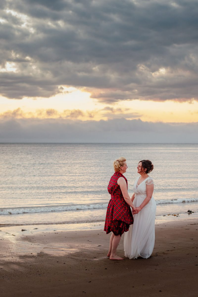 two brides on portmahomack beach watching the sunset scottish highlands wedding photographer