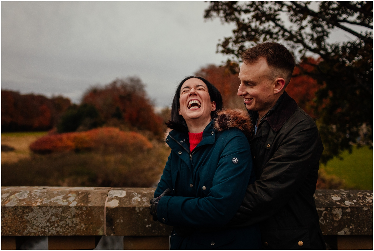 Couple in Pollok Park in Autumnstanding on bridge beside pollok house laughing couples shoot engagement shoot