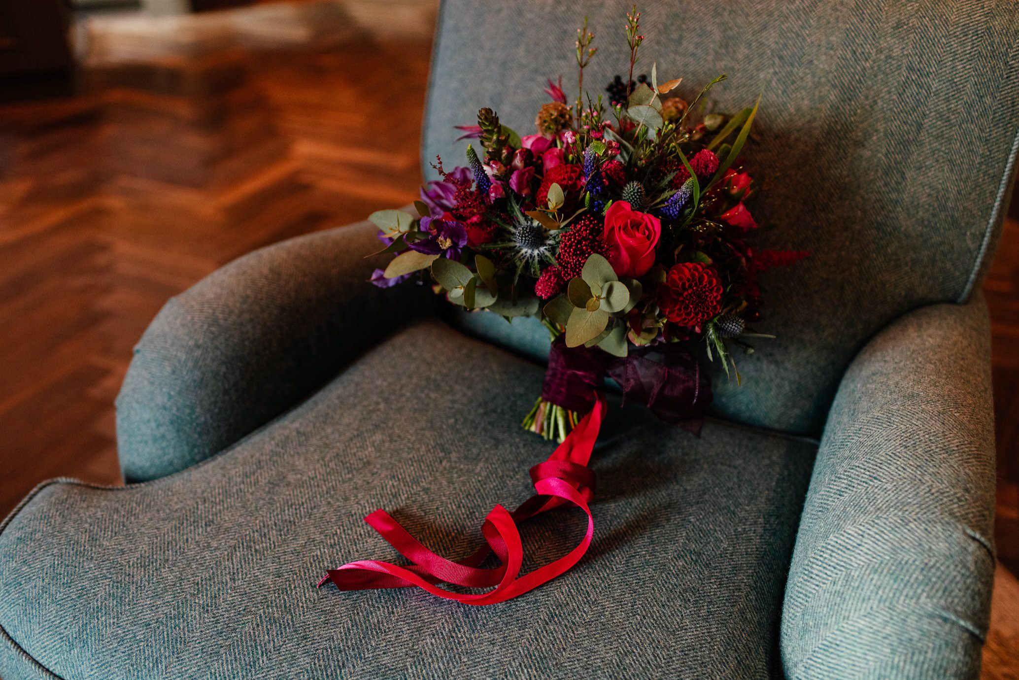 lush red purple wedding bridal bouquet with pink ribbons on grey chair