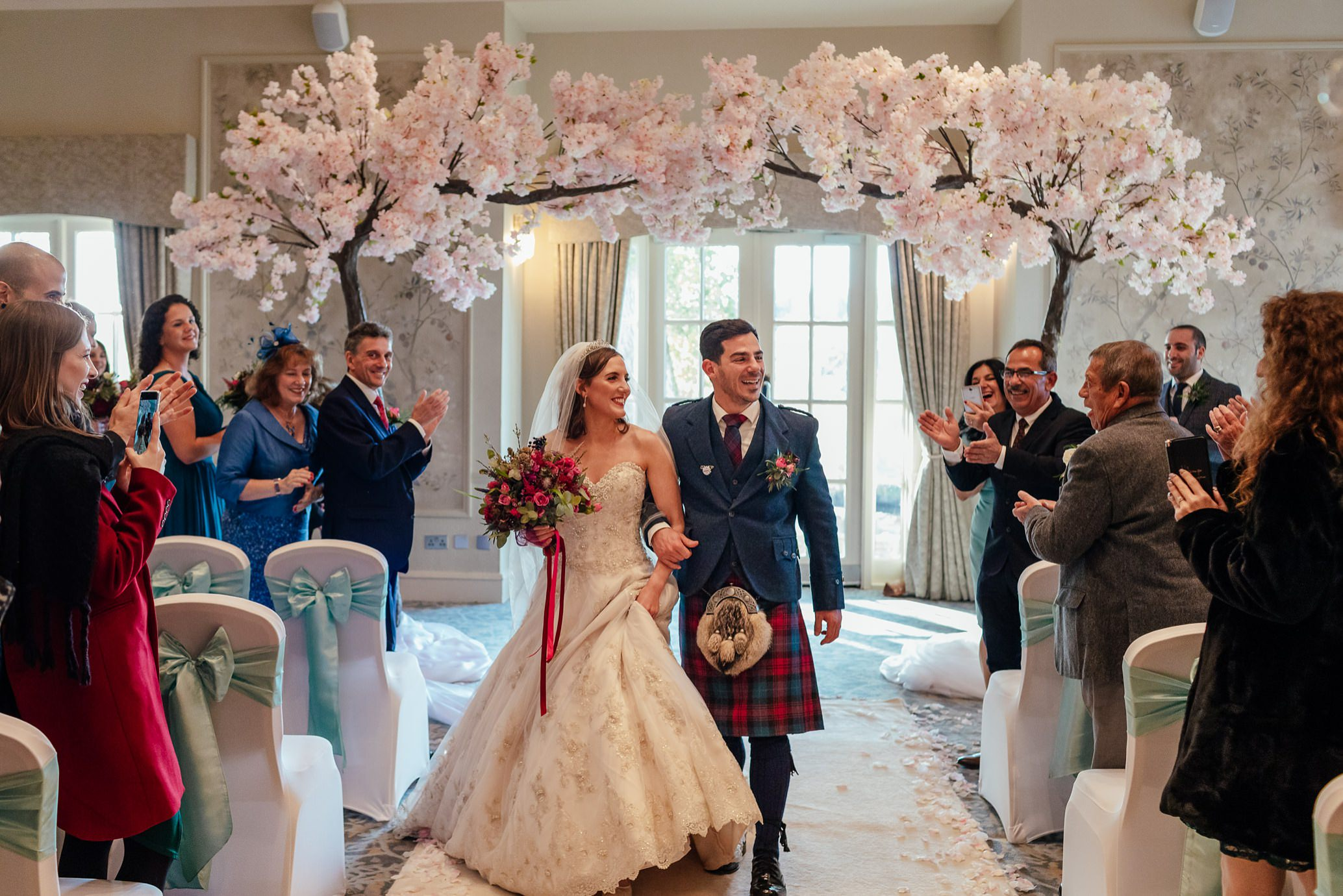 maryculter house hotel aberdeenshire wedding ceremony in ballroom with cherry blossoms bride groom walking down aisle