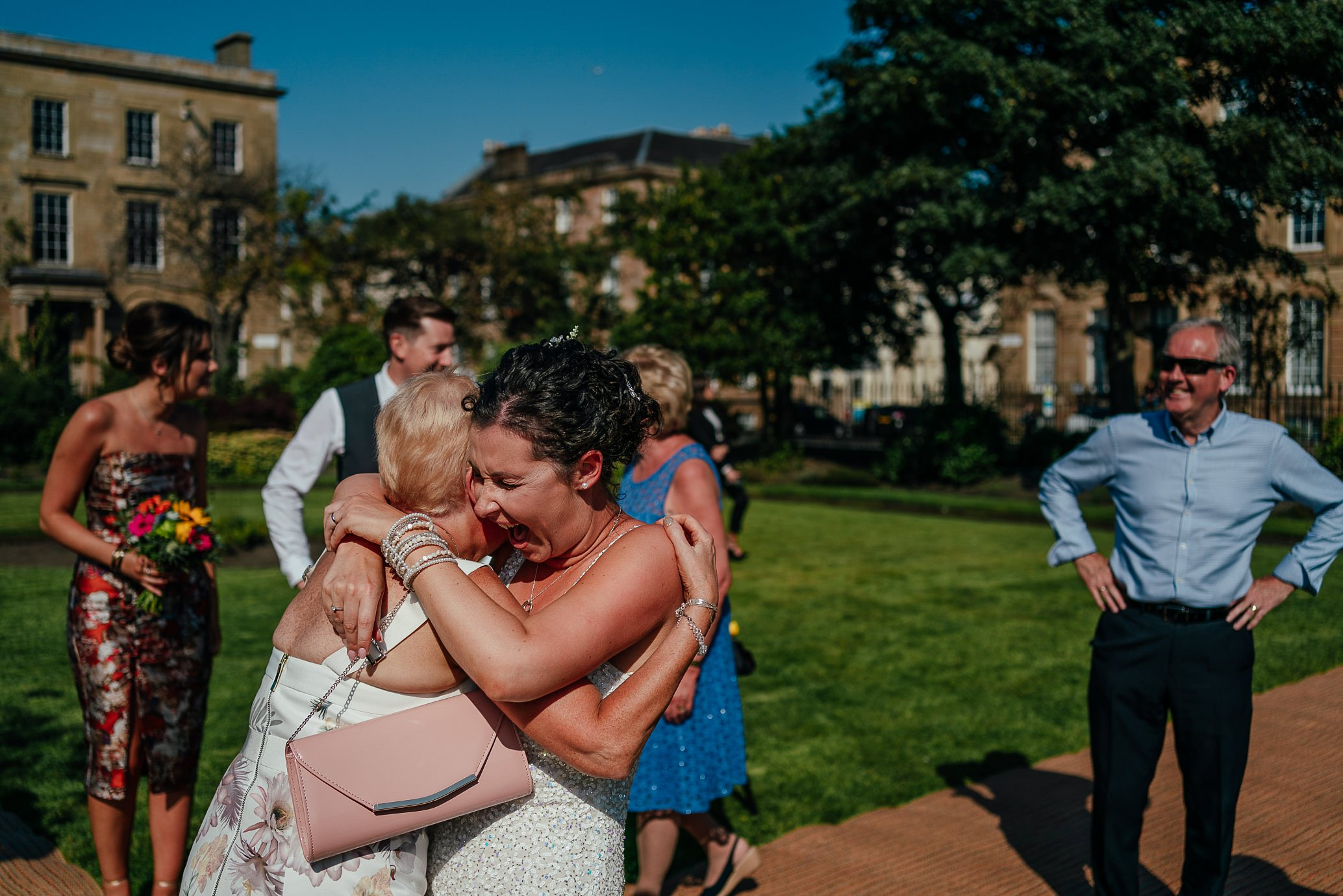 blythswood square glasgow private gardens wedding ceremony bride hugging mum after wedding ceremony laughing