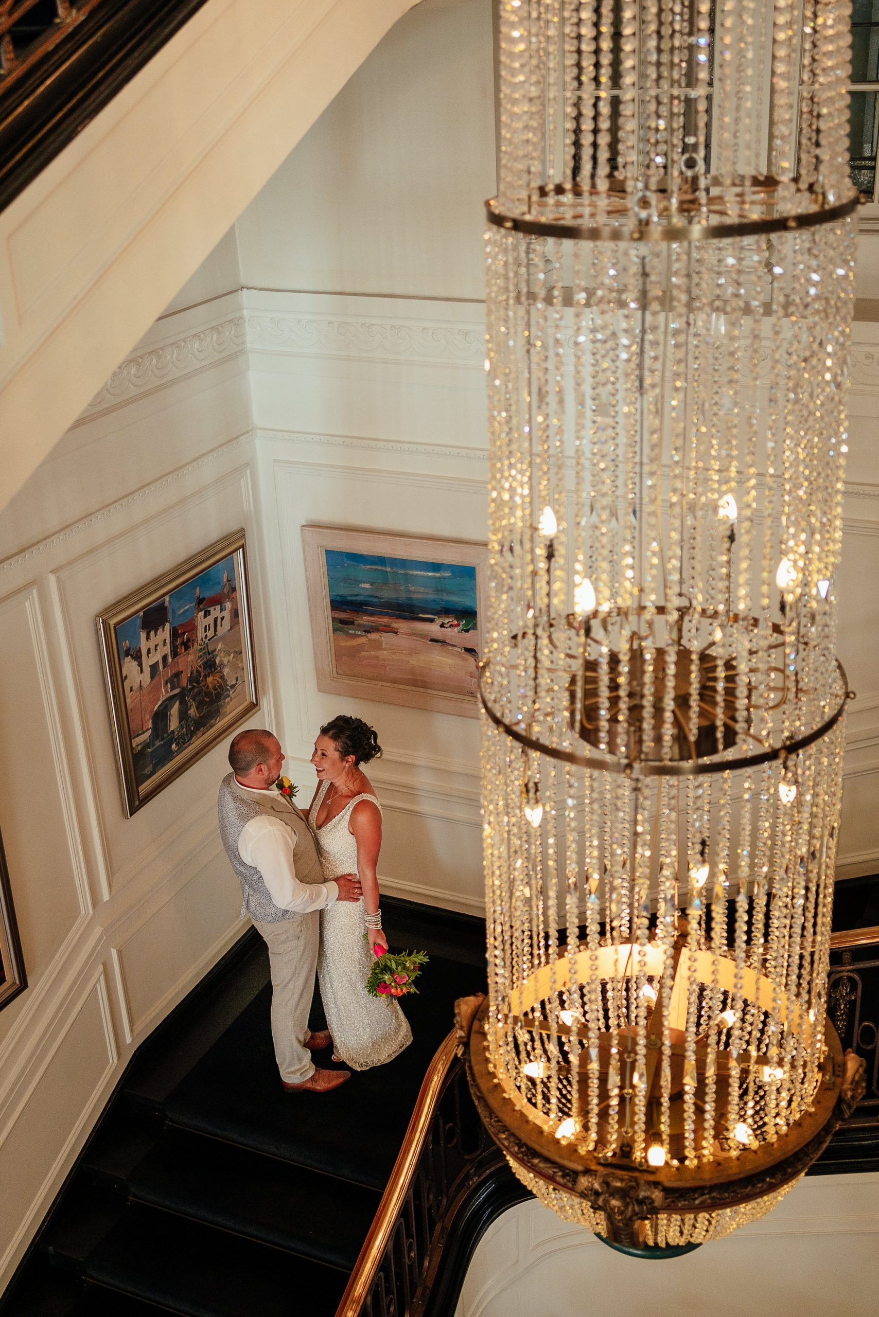 blythswood square glasgow private gardens wedding ceremony bride groom by chandelier indoors at blythswood hotel staircase